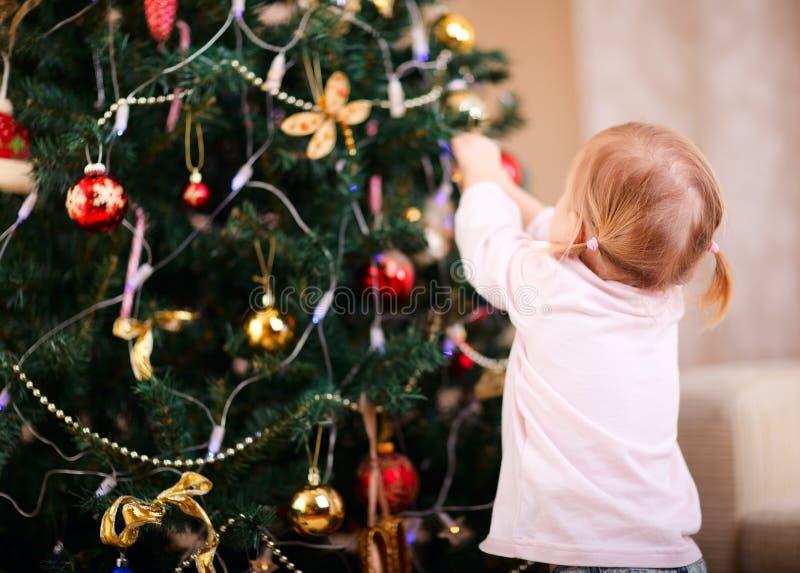 Bambina che decora l'albero di Natale fotografia stock libera da diritti