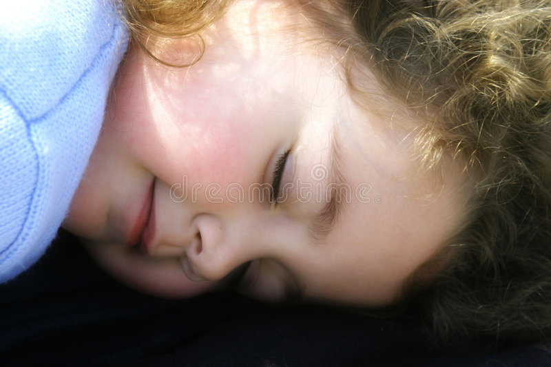 Bambina che dorme al sole immagine stock