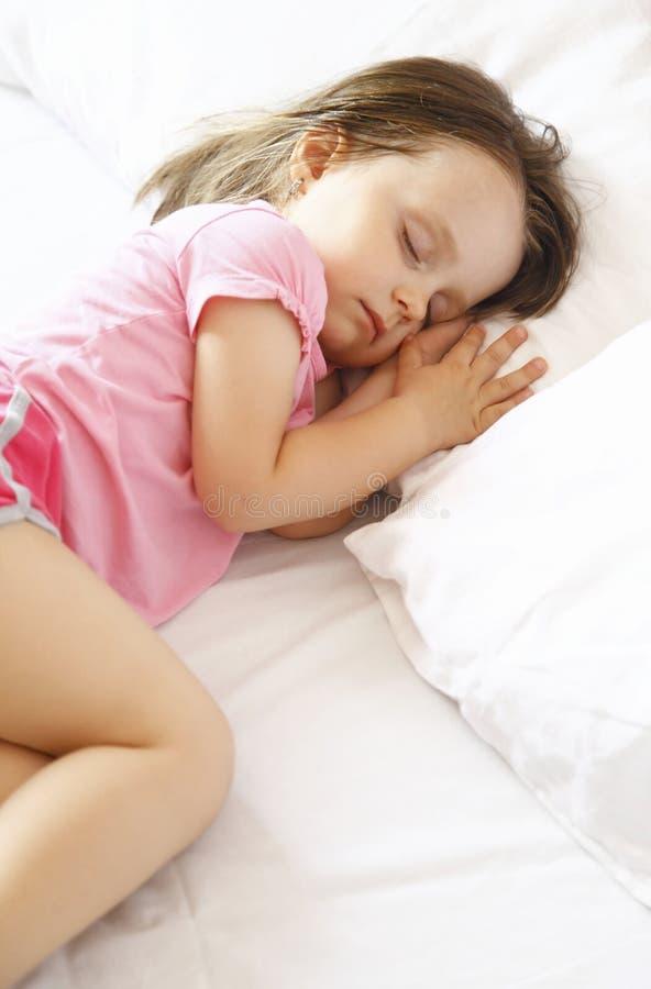 Bambina che dorme pacificamente a letto immagini stock libere da diritti