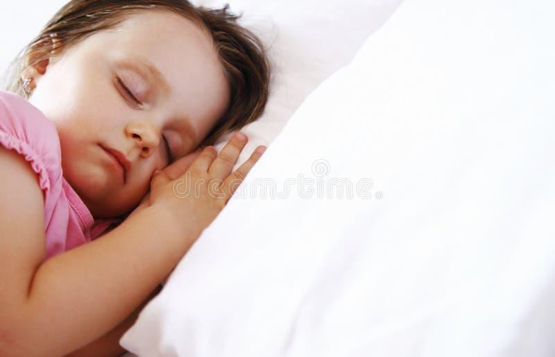 Bambina che dorme pacificamente a letto fotografia stock libera da diritti