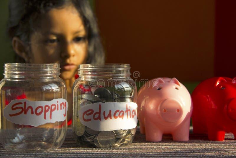 Bambina che esamina i barattoli dei soldi identificati come acquisto e istruzione con i porcellini salvadanaio, Pune, India immagini stock