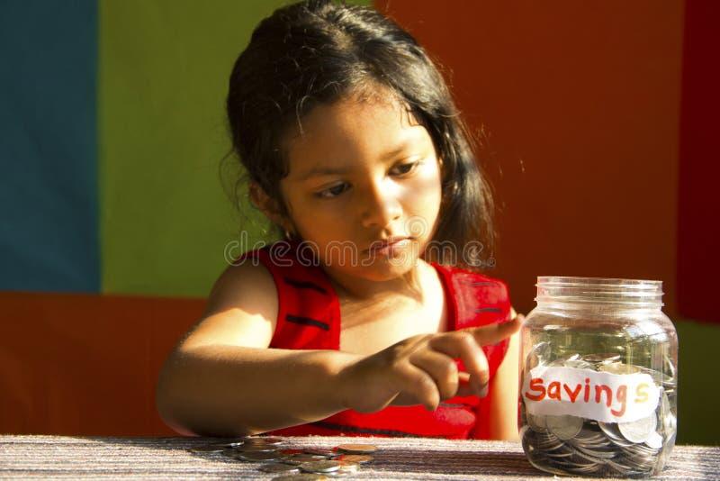 Bambina che esamina il barattolo dei soldi riempito di monete ed identificato come salvataggio della Pune, India immagine stock libera da diritti