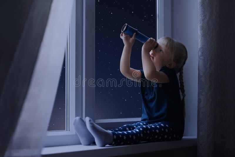 Bambina che esamina il cielo in pieno delle stelle fotografie stock libere da diritti