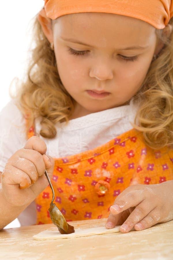 Bambina che fa la serie dei biscotti fotografie stock