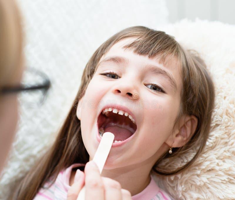 Bambina che fa la sua esaminare gola dal professionista del settore medico-sanitario fotografia stock