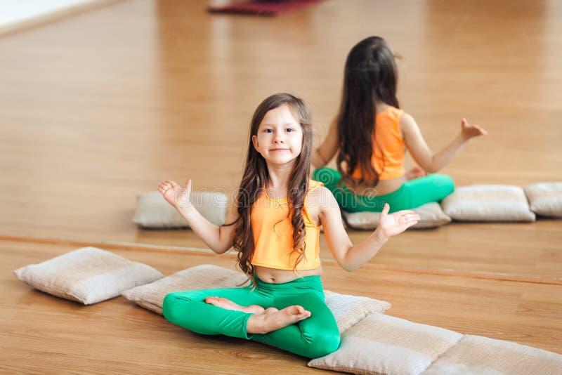 Bambina che fa yoga, ritratto di piccola yoga di pratica sorridente sveglia della ragazza, in un vestito arancio fotografie stock