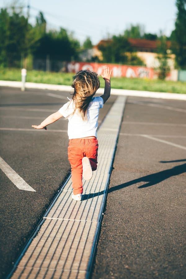 Bambina che fugge sulla strada fotografia stock libera da diritti
