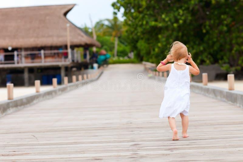 Bambina che funziona sul molo fotografie stock libere da diritti