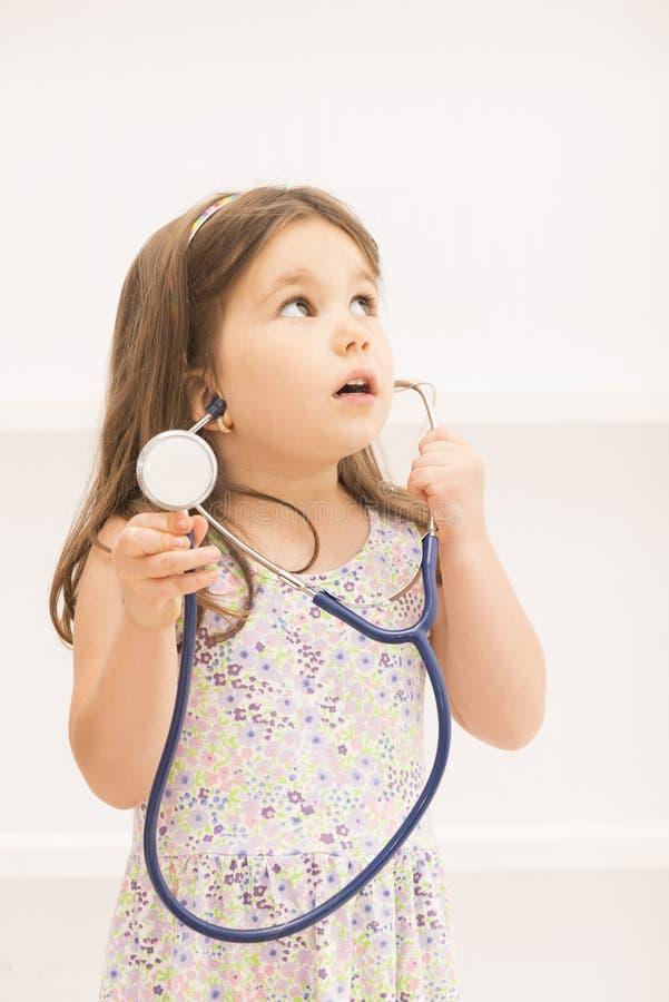 Bambina che gioca al dottore con lo stetoscopio immagine stock libera da diritti