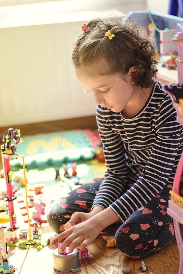 Bambina che gioca con i giocattoli nella sua stanza fotografia stock libera da diritti