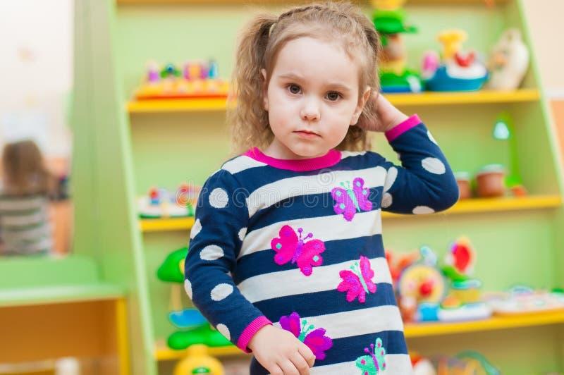 Bambina che gioca con i giocattoli in stanza dei giochi immagini stock libere da diritti