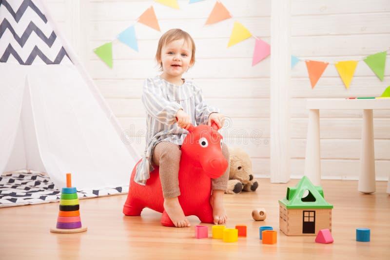 Bambina che gioca con il cavallo rosso del giocattolo a casa immagini stock libere da diritti
