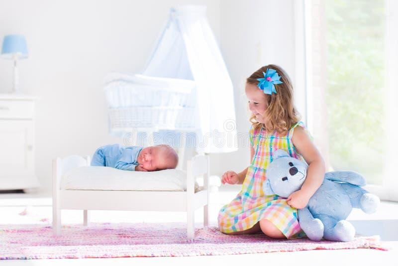 Bambina che gioca con il fratello del neonato fotografia stock