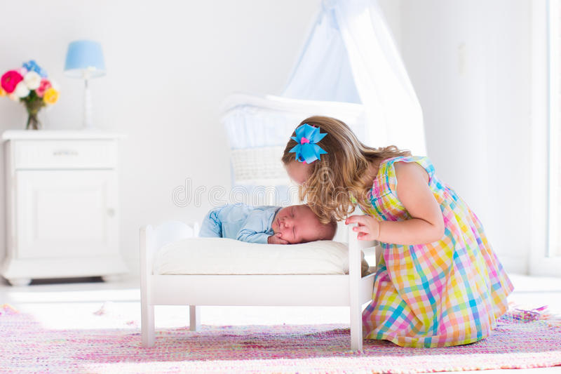 Bambina che gioca con il fratello del neonato immagini stock libere da diritti
