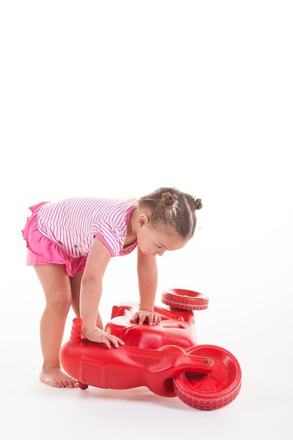 Bambina che gioca con il suo motorino rosso immagini stock