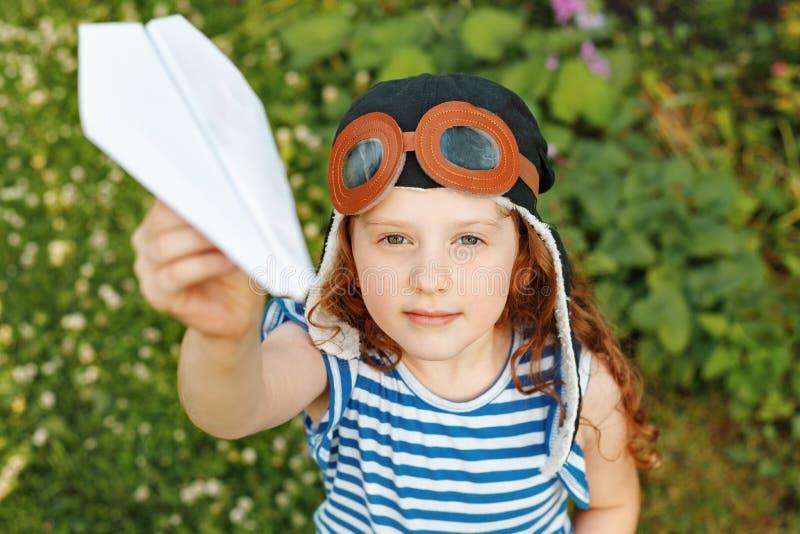 Bambina che gioca con l'aeroplano di carta nel parco di estate fotografie stock