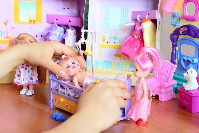 Bambina che gioca con le bambole Ragazza che tiene una bambola in sua mano Bambole, mobilia del giocattolo, vestiti su una tavola fotografie stock