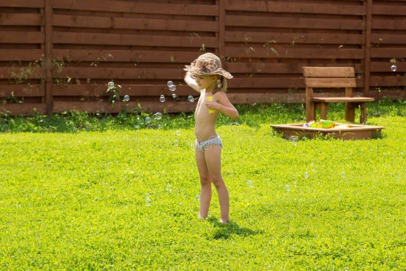 Bambina che gioca con le bolle di sapone fotografie stock libere da diritti