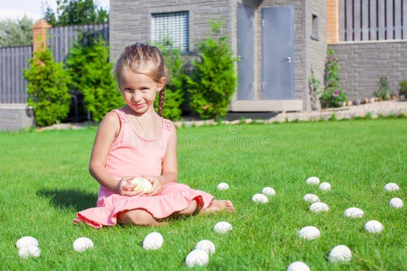 Bambina che gioca con le uova di Pasqua bianche in fotografie stock