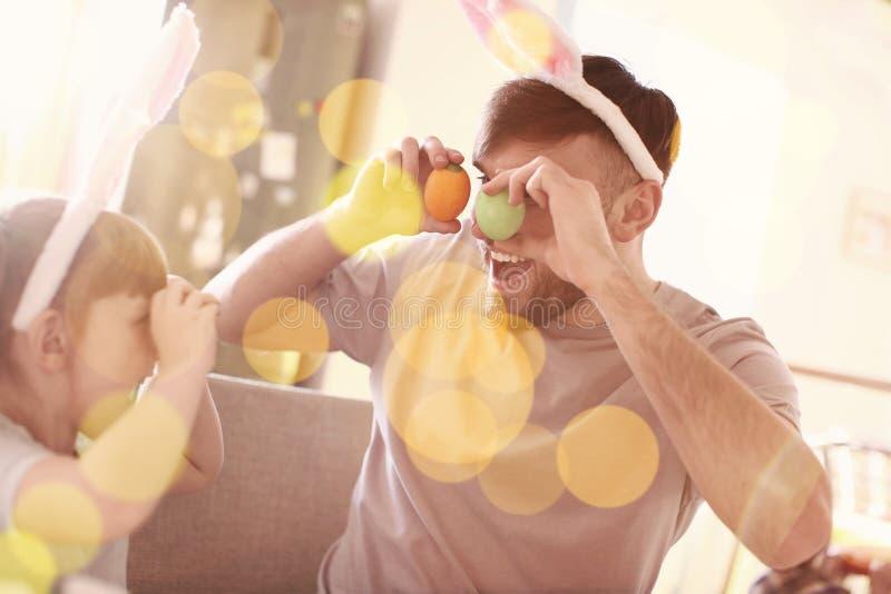 Bambina che gioca con suo padre mentre dipingendo le uova di Pasqua a casa immagini stock libere da diritti