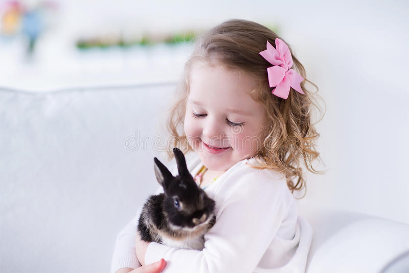 Bambina che gioca con un coniglio reale dell'animale domestico fotografia stock