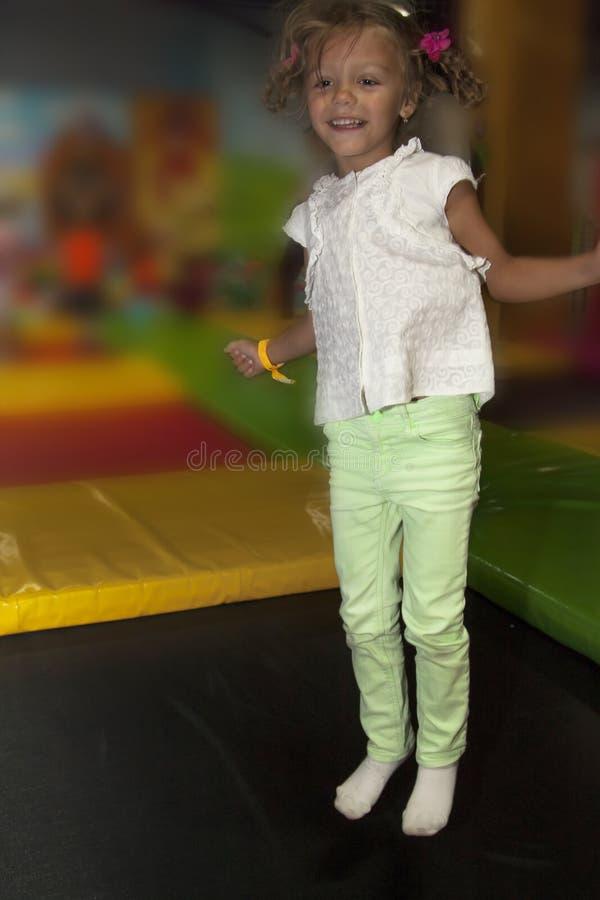 Bambina che gioca e che si diverte sul trampolino in bambini fotografia stock