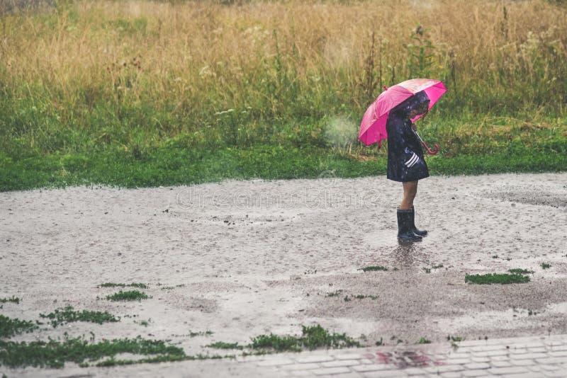 Bambina che gioca esterno solo in maltempo immagine stock