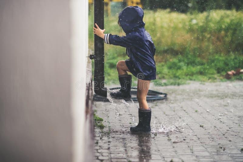 Bambina che gioca esterno solo in maltempo fotografia stock libera da diritti