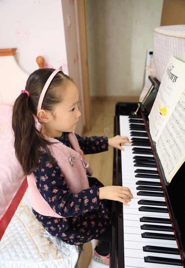 Bambina che gioca il piano a casa fotografie stock libere da diritti