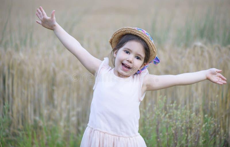 Bambina che gioca nel giacimento di grano fotografia stock