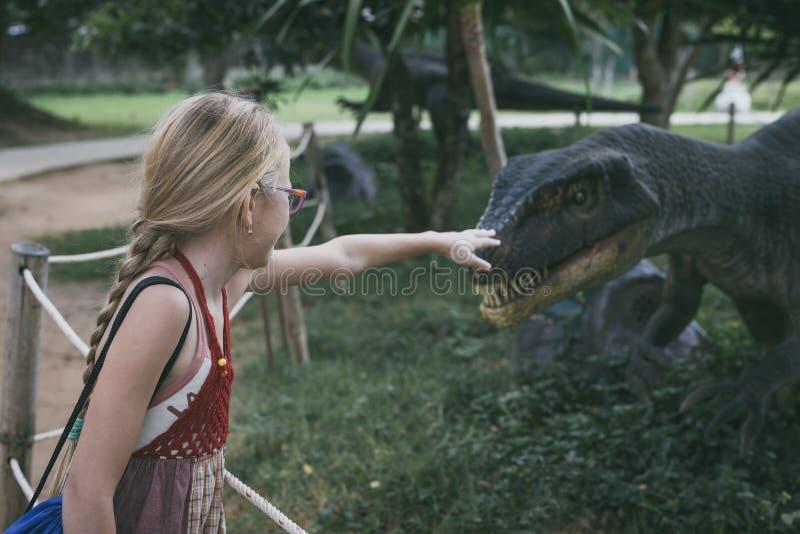 Bambina che gioca nel parco di Dino di avventura fotografia stock