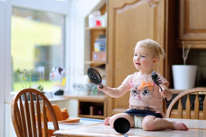 Bambina che gioca nella cucina fotografia stock