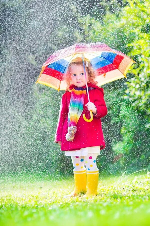 Bambina che gioca nella pioggia fotografia stock