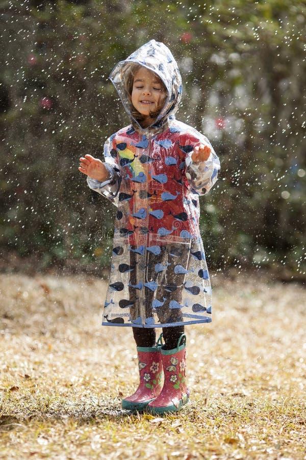 Bambina che gioca nella pioggia fotografia stock libera da diritti