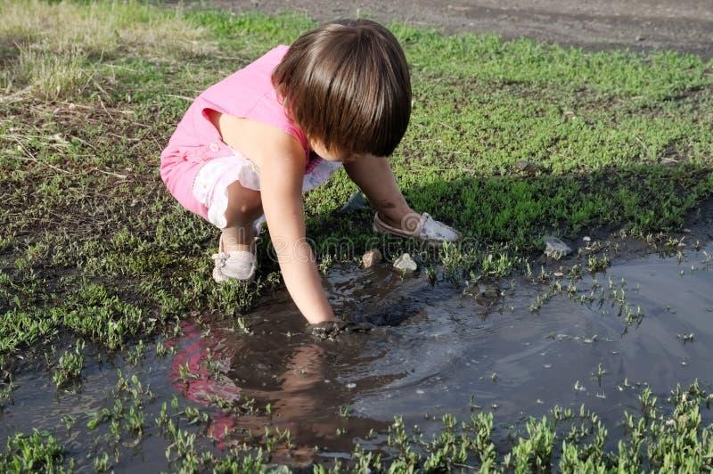 Bambina che gioca nella pozza all'estate Pozza nera della sporcizia dopo pioggia Mondo d'esplorazione di dintorni fotografia stock
