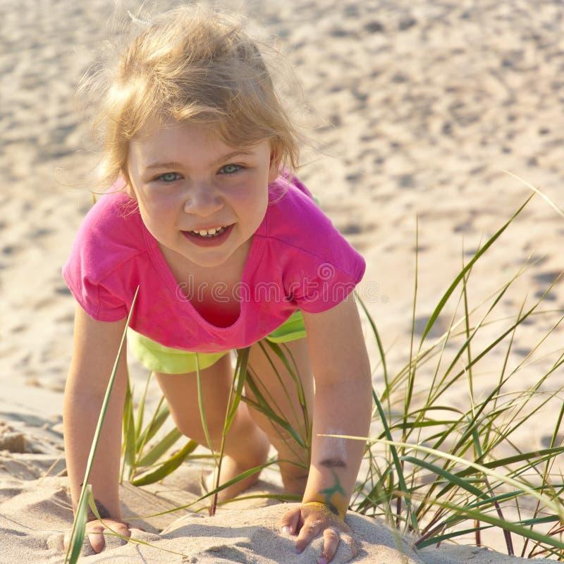 Bambina che gioca nella sabbia della spiaggia fotografie stock libere da diritti