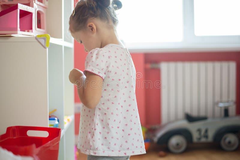 Bambina che gioca nella stanza del bambino immagini stock