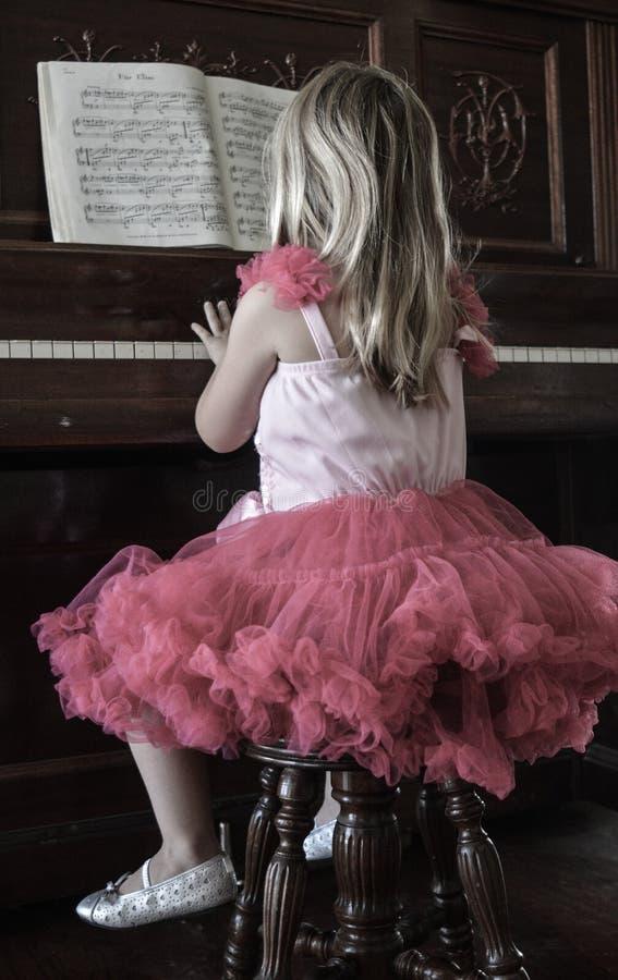 Bambina che gioca piano fotografia stock