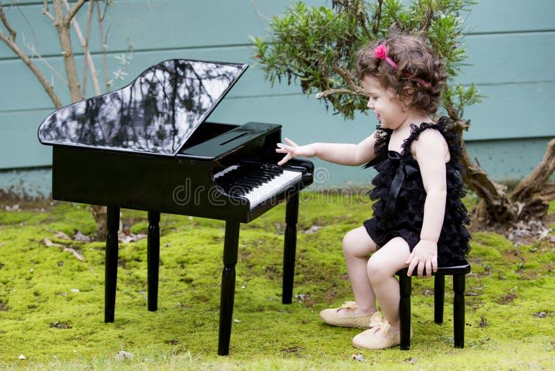 Bambina che gioca sul piano del giocattolo fotografia stock libera da diritti