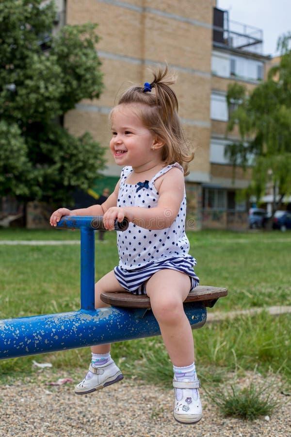 Bambina che gioca sulla bascula fotografia stock