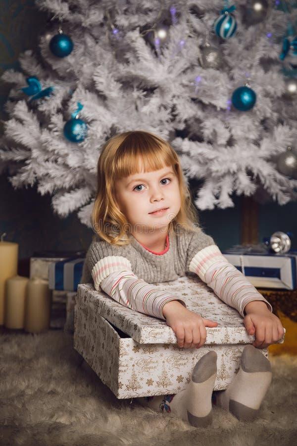 Bambina che giudica presente vicino all'albero di Natale fotografia stock libera da diritti