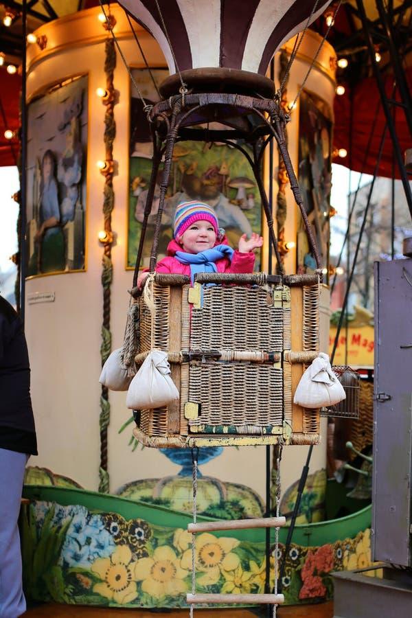 Bambina che gode del girotondo durante la luna park fotografia stock libera da diritti