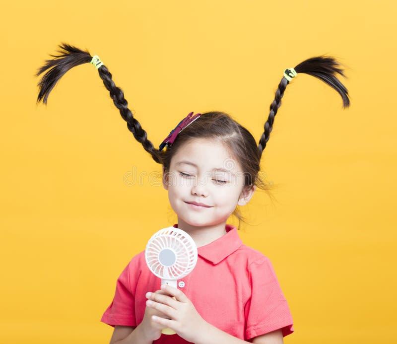 Bambina che gode del vento fresco dall'elettroventola fotografia stock
