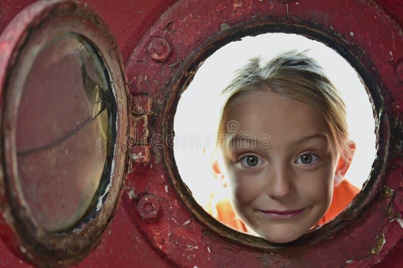 Bambina che guarda da un vecchio oblò fotografia stock