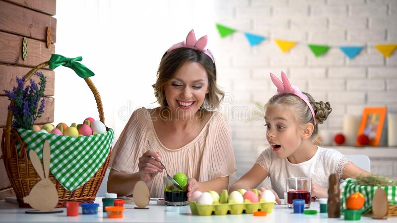 Bambina che guarda emozionante madre immergere uovo nel colorante alimentare verde, Pasqua fotografia stock