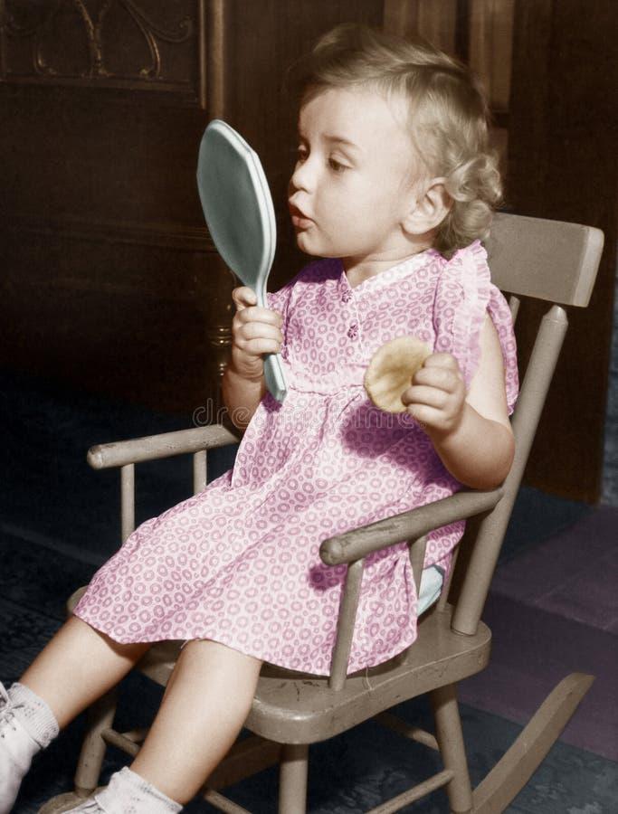 Bambina che guarda in specchio fotografie stock
