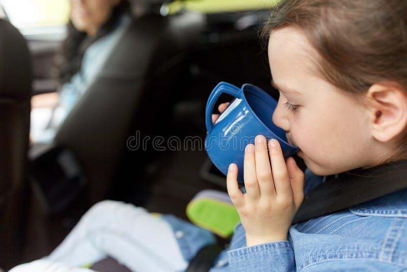 Bambina che guida in automobile e che beve dalla tazza immagini stock libere da diritti