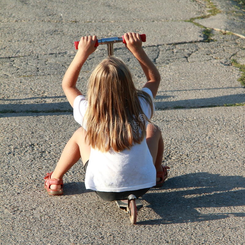 Bambina che guida un motorino immagini stock