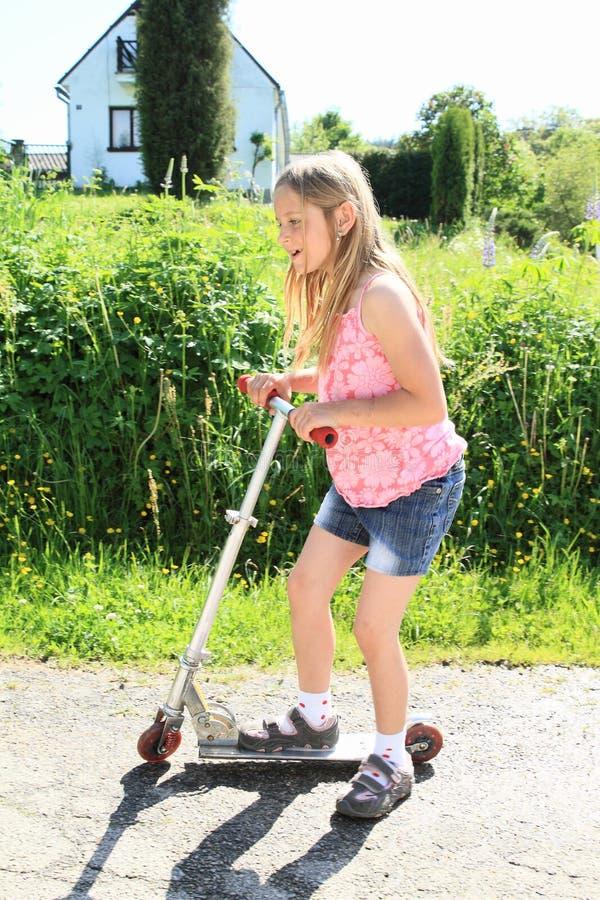 Bambina che guida un motorino fotografia stock