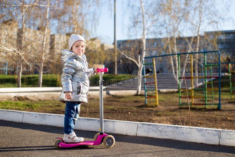 Bambina che guida un motorino nel parco un giorno di molla soleggiato Svago attivo e sport all'aperto per i bambini immagini stock libere da diritti